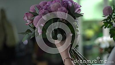 Vista posterior de una adorable florista mujer joven que viste delantal componer un nuevo ramo metrajes