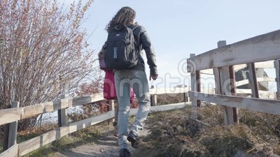 Vista posterior de una joven pareja multirracial con mochilas subiendo por la valla en el parque de otoño novio y metrajes