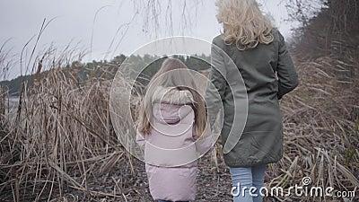Vista posterior de una mujer caucásica caminando hacia el lago o río a través de arbustos Madre rubia e hija morena almacen de metraje de vídeo