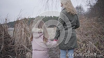 Vista posterior de una mujer rubia adulta y una niñita morena parada en arbustos de otoño frente al lago o el río caucásico almacen de metraje de vídeo