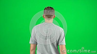 Vista posterior del hombre caminando y saludando en una pantalla verde, Chroma Key almacen de metraje de vídeo