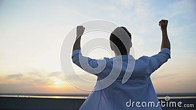 Vista posterior del hombre caucásico levantando manos al cielo sobre fondo de puesta de sol, motivación almacen de video