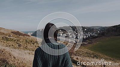 Vista posteriore bellissima donna turista che cammina lungo la collina vicino a splendide Etretat mare rocce, capelli scuri che s stock footage