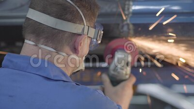 Vista posteriore di un operaio caucasiano maschio che utilizza un tritacarne metallico Professionista che lavora in officina di r stock footage