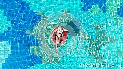 Vista superior de la piscina con una mujer en un anillo de natación Concepto de vacaciones de verano almacen de video