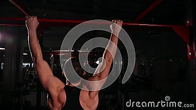 A vista traseira, a câmera move-se atrás do atleta apropriado à barra executar tração-UPS filme