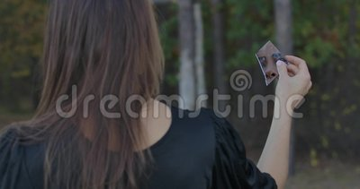 Vista traseira de uma garota caucasiana segurando fragmento de espelho quebrado Seu rosto refletindo no crack Mulher misteriosa c vídeos de arquivo