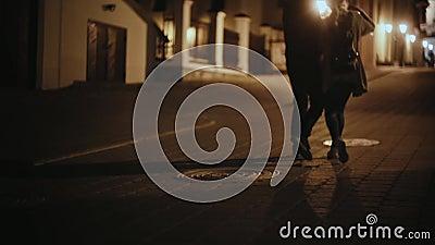 Vista trasera de los pares elegantes que caminan en el centro de ciudad en la igualación junto Hombre y mujer fecha romántica metrajes