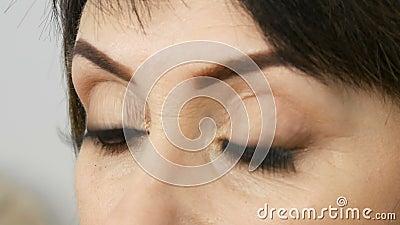 Vista vicina degli occhi azzurri con le frecce e dei cigli falsi lunghi della donna adulta di mezza età con bello trucco in a video d archivio