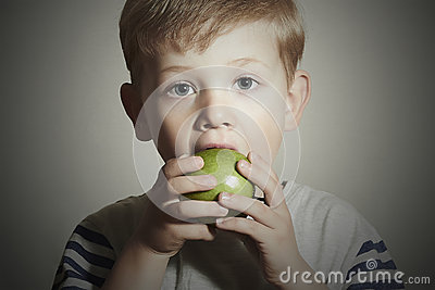 Vitamin.Child eating apple.Little Boy with green apple. Health food. Fruits