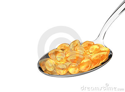 Vitamin pills on spoon