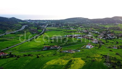 Vliegen boven de heuvels van het groene platteland met dorpshuizen nabij Limassol district Limassol, Cyprus stock videobeelden