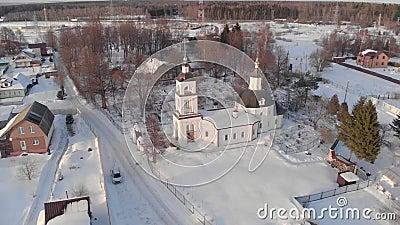 Vliegen in de winter over de kerk bij duidelijk weer bij dageraad vanaf de hoogte stock footage