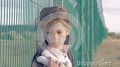 Vluchtelings dakloos kind portret die van Kaukasisch meisje zich voor metaalomheining bevinden, is zij ongelukkig en boos stock videobeelden