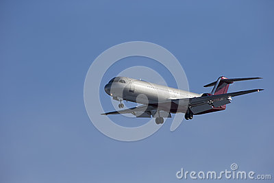 Passenger plane sits isolated on a blue sky background.