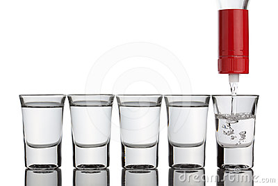 Vodka pouring into shot glasses standing in row.