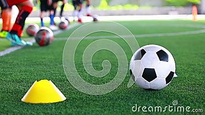 Voetbalbal op groen kunstmatig gras tussen kegelsmaker met onscherpe voetbalteam opleiding stock video