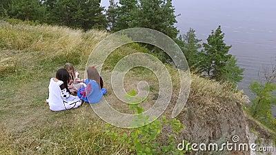 Vogelperspektive von drei Freundinnen in den langen Kleidern mit dem Unterhaltungsc$sitzen der Stickerei im Gras auf dem hohen Hü stock footage