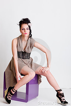 Vogue style girl posing on modern chair in studio