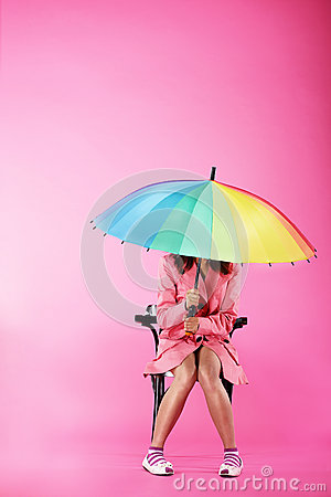Vogue. Woman in Pink Coat sitting with Colorful Umbrella