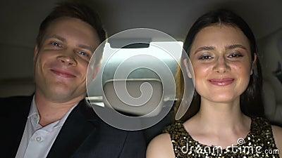 Voiture de célébrités souriantes, hommes et femmes, avant l'événement glamour, mode de vie luxueux banque de vidéos