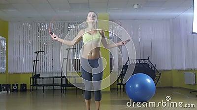 Volledig lengteportret van een vrolijke vrouw die oefeningen met touwtjespringen doen die op een witte achtergrond worden geïsole stock video