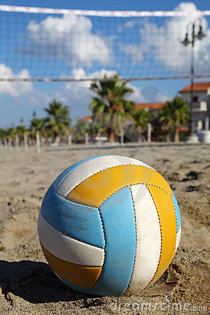 Volleyball net, volleyball on beach and palm trees