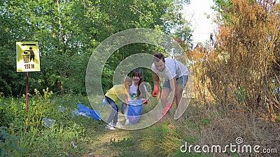 Volontari della famiglia, giovane madre e padre con le cure della ragazza del bambino circa la natura di ecologia e raccogliere r video d archivio
