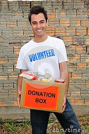 Voluntario feliz con el rectángulo de la donación del alimento