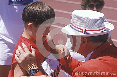 Volunteer coaching handicapped young athlete Editorial Stock Image