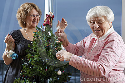 Volunteer helping senior decorate her Christmas Tr