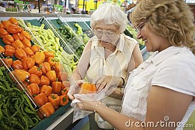 Volunteer helping senior with her shopping