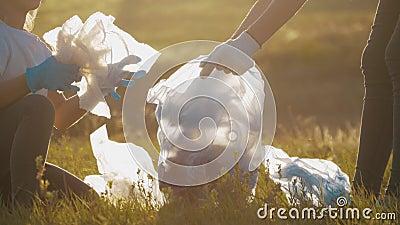 Volunteer teamfamilie pakt afval op en plastics schoonmaken het park met een vuilniszak Teamwerk en ecologie stock videobeelden