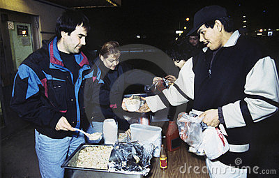 Volunteers And Homeless At Soup Kitchen