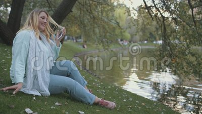 Voman Plus Size Talk Smartphone Sit op River Bank stock footage