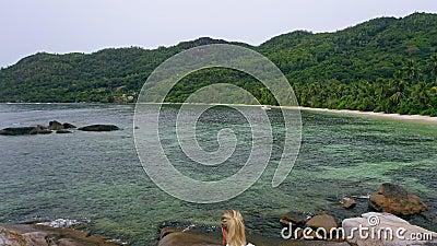 Voo aérea revela imagens com uma menina loira sentada em rocha granita contra lagoa tropical exótica na ilha do paraíso vídeos de arquivo