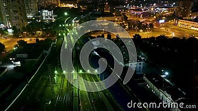 Voo noturno sobre os comboios em movimento na estação ferroviária central e na estrada com a ponte de uma grande cidade Foto de 4 filme