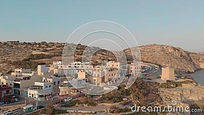 Voo sobre a estância turística bonita com hotéis e a estrada para o tráfego no litoral rochoso perto da água contra o céu vídeos de arquivo
