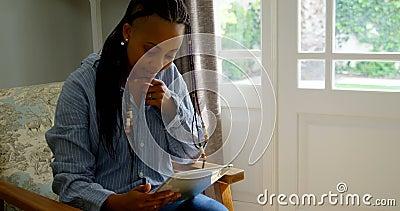 Vooraanzicht van jong zwarte die digitale tablet in woonkamer van comfortabel huis 4k gebruiken stock footage