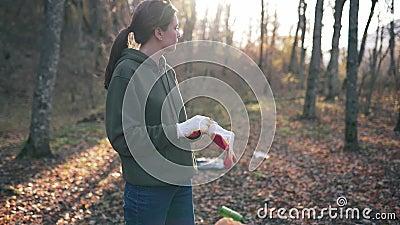Voorbereiding van de inzameling van afval en plastic afval in het herfstbos Jonge vrouw zet zich op handschoenen stock videobeelden