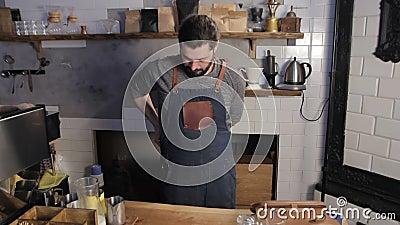 Vor dem Beginnen der Arbeit im Kaffeehaus Barista trägt ein Schutzblech Ein bärtiger Mann kleidet in einer schützenden Uniform an stock footage