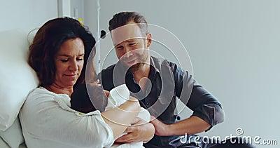 Vorderansicht des kaukasischen Ehepaares, das sein Neugeborenes im Krankenhaus in der Krankenstation hält stock video