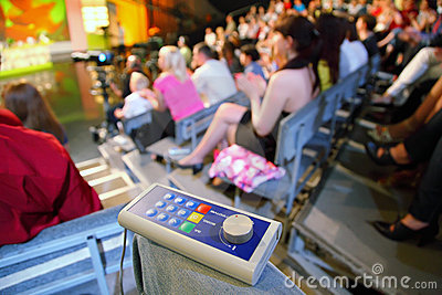 Voting device lies on knee in auditorium Editorial Stock Photo