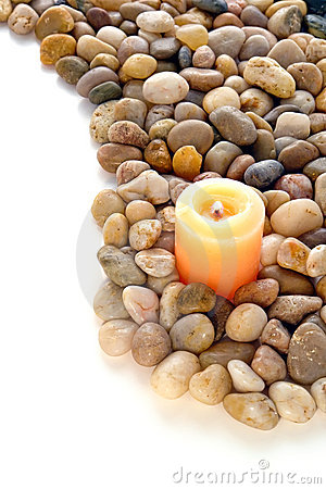 Votive Candle Burning in Bed of Pebbles over White