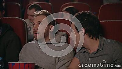 Vrienden die film in bioskoop wathcing Mens die aan vrienden verhinderen die op film letten stock footage