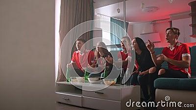 Vrienden kijken naar sport op tv, juichen en vieren Fijne supporters zitten op de bank met popcorn en drankjes stock videobeelden