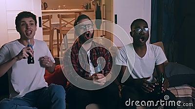Vriendschap en entertainment concept, multi-etnische jonge mannelijke voetbalfans die naar het grote spel kijken bij langzame bew stock videobeelden