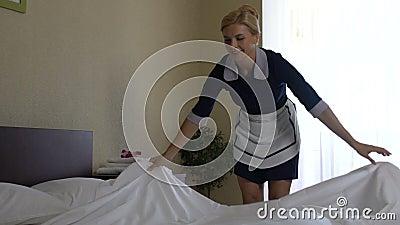 Vriendschappelijk hotelmeisje die zorgvuldig haar doen bed-maakt plichten, slow-motion baan, stock videobeelden