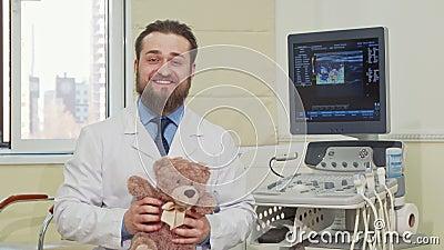 Vriendschappelijk mannelijk de teddybeerstuk speelgoed van de pediaterholding, die aan de camera golven stock footage