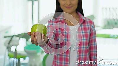 Vriendschappelijk meisje die appel in tandbureau, gezond tandenconcept, vitaminen aanbieden stock video